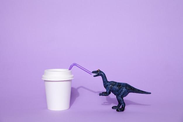 빨대로 플라스틱 컵에서 마시는 장난감 공룡