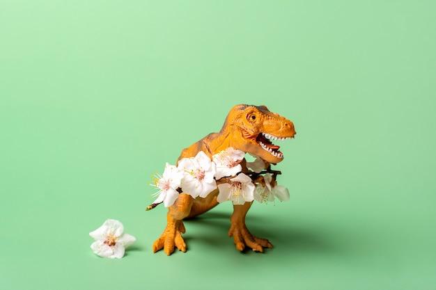 녹색 배경에 발에 살구 꽃을 들고 장난감 공룡 티라노사우루스