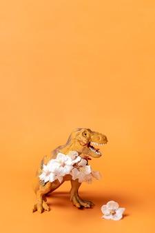 오렌지 배경에 발에 살구 꽃을 들고 장난감 공룡 티라노사우루스