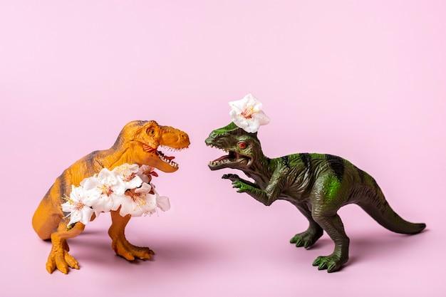 발에 살구 꽃을 들고 장난감 공룡 티라노사우루스