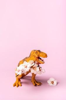 발에 살구 꽃을 들고 장난감 공룡 티라노사우루스 프리미엄 사진