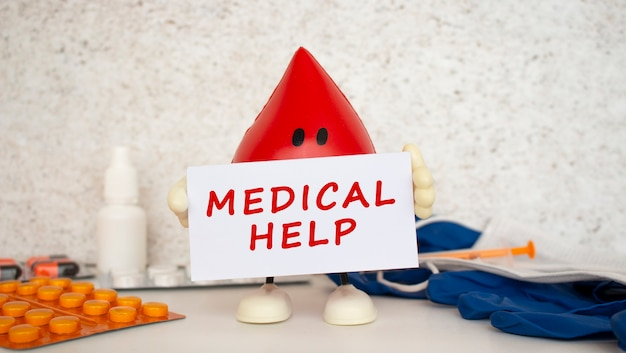 A toy drop of blood holds a white business card with the inscription. medical concept.