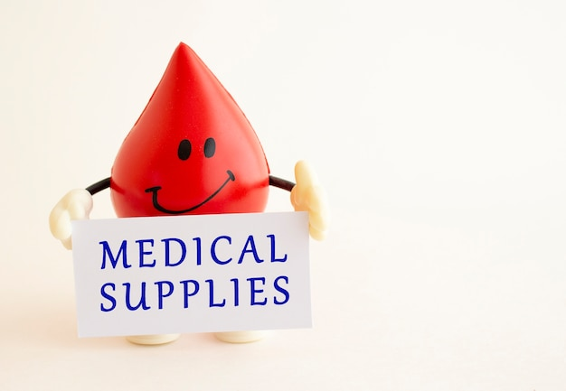A toy drop of blood holds a white business card with the inscription.