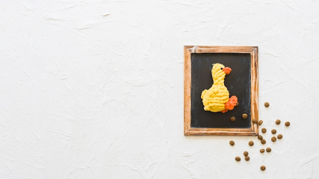 Toy duck and pet food on chalkboard