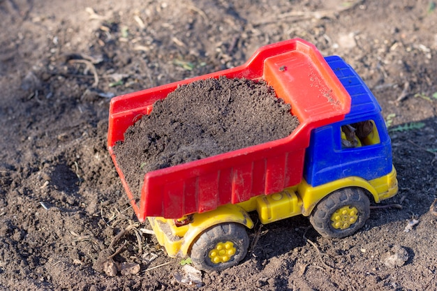 おもちゃのダンプトラックは砂でいっぱいの地面に立っています。