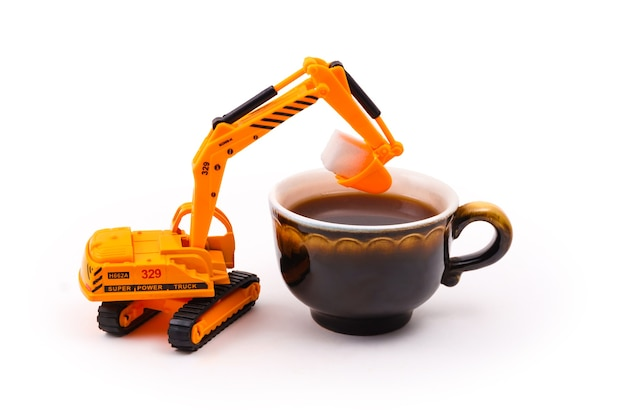 장난감 굴착기는 밝은 배경에 있는 실제 커피 한 잔에 큐브 설탕을 넣습니다.