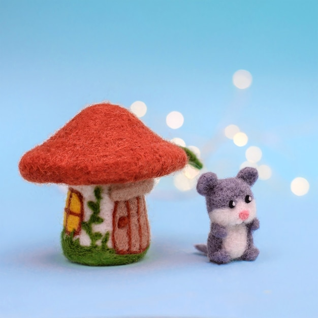 Toy felt house mushroom with a door and windows and a cute little gray mouse on a light blue background with bokeh
