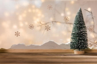 Toy fir tree on wood table near bank of snow, plant twig, snowflakes and fairy lights