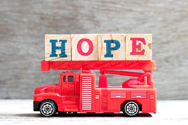 Toy fire ladder truck hold letter block in word hope on wood background
