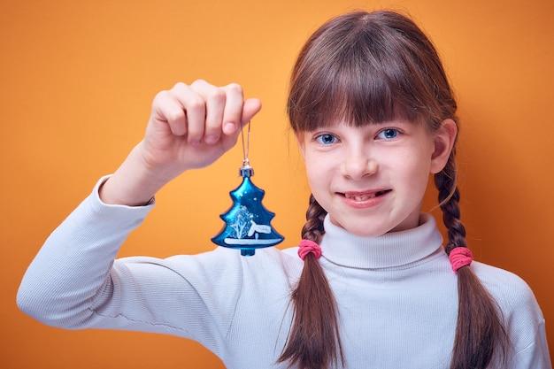 Игрушка на елку у кавказской девушки в руке на цветном