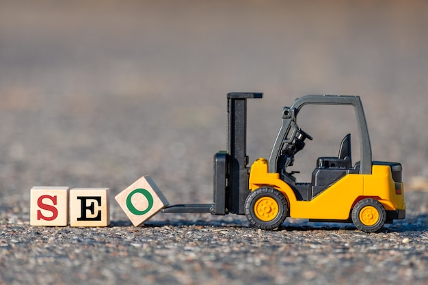 A toy forklift lifts a block with the  letter o to complete the word seo (search engine optimization abbreviation) from the asphalt.