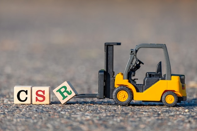 A toy forklift lifts a block with the letter r in csr
