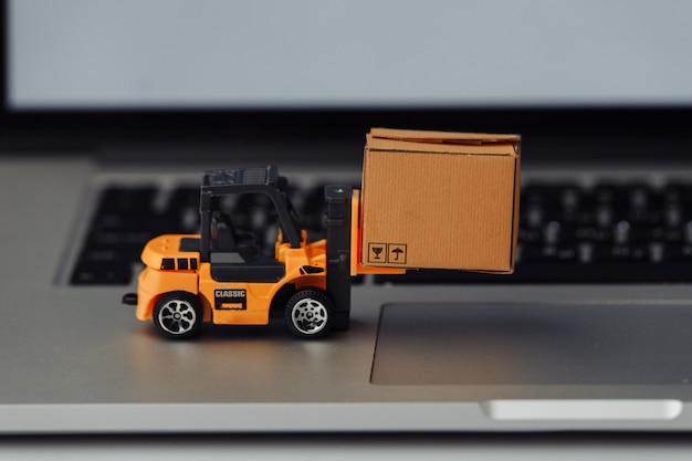 Toy forklift with box on a keyboard. logistics and wholesale concept