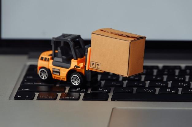 Игрушечный вилочный погрузчик с коробкой на крупном плане клавиатуры. логистика и оптовая концепция.
