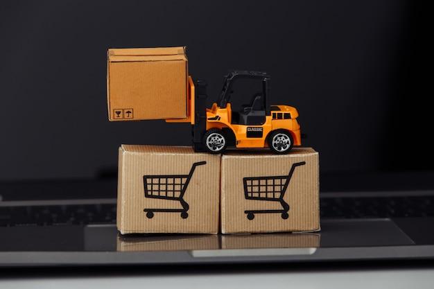 노트북에 판지 상자 장난감 지게차. 물류 및 도매 개념.