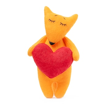 Toy fox holding red heart pillow isolated