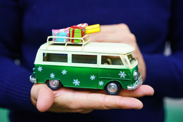 A toy green holiday bus with gifts on the roof stands on your hand . christmas tree decor