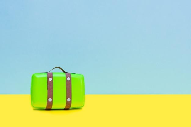 파란색 배경과 노란색 바닥에 장난감 녹색 가방. 여행 개념.