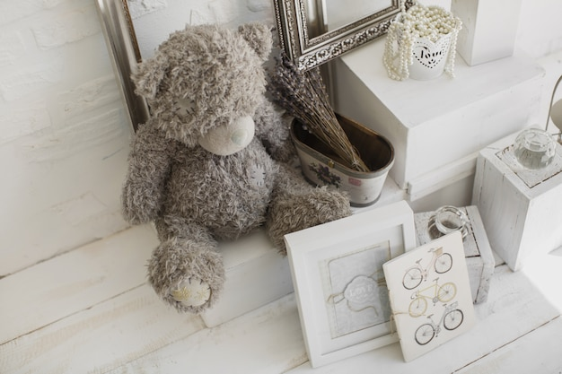 Toy grey bear in a white photo studio. paintings, beads, frames, bike.