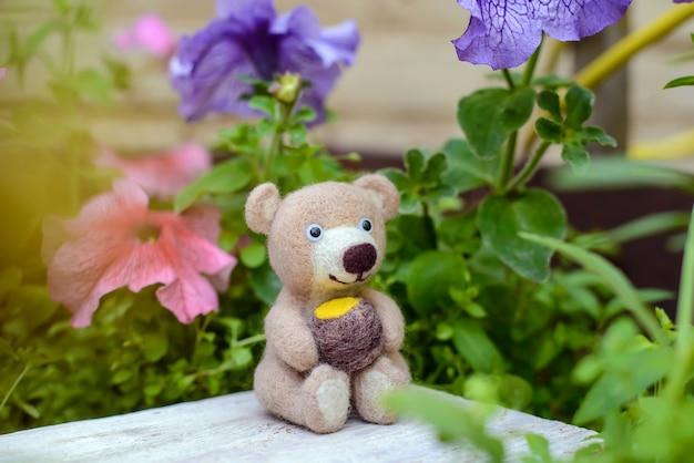 おもちゃの手作りのかわいいクマは、花の間に蜂蜜の樽、フェルトウールと一緒に座っています