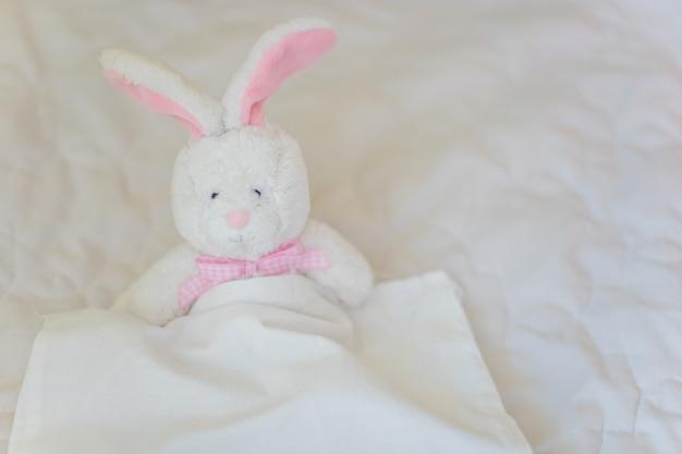 장난감 토끼는 흰색 침대에 있습니다. 어린이 역할 놀이 게임에서 부드러운 장난감 토끼.