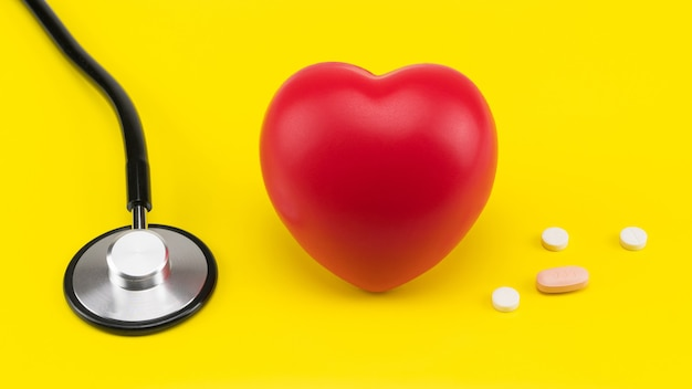 おもちゃの心臓と黄色の背景の聴診器心臓の心臓病のケア
