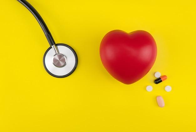おもちゃの心臓と黄色の背景の聴診器上面図心臓の心臓病のケア