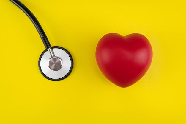 おもちゃのハートと黄色の背景に聴診器。上面図。コンセプトヘルスケア。心臓病学-心臓のケア