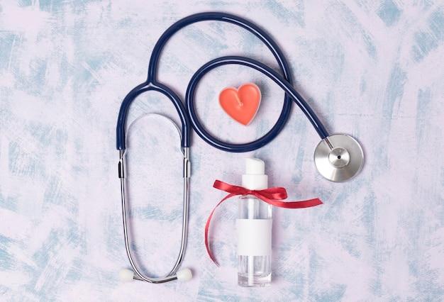 おもちゃの心臓と医療聴診器と青い背景の消毒剤、上面図