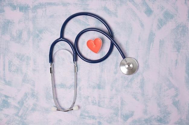 青い背景、上面図におもちゃの心臓と医療聴診器