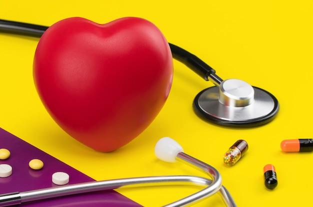 色付きの背景におもちゃの心臓と聴診器心臓の心臓病のケア