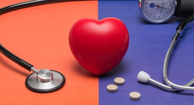 色付きの背景におもちゃの心臓と聴診器コンセプトヘルスケア心臓病心臓のケア