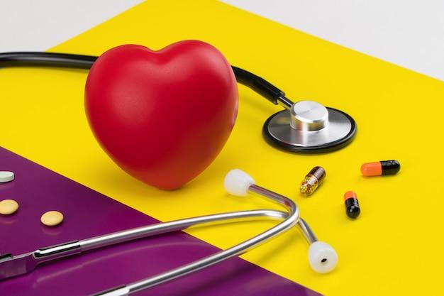 色付きの背景におもちゃのハートと聴診器。コンセプトヘルスケア。心臓病学-心臓のケア