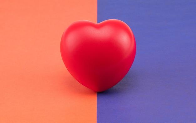 色付きの背景におもちゃのハート。コンセプトヘルスケア。心臓病学-心臓のケア