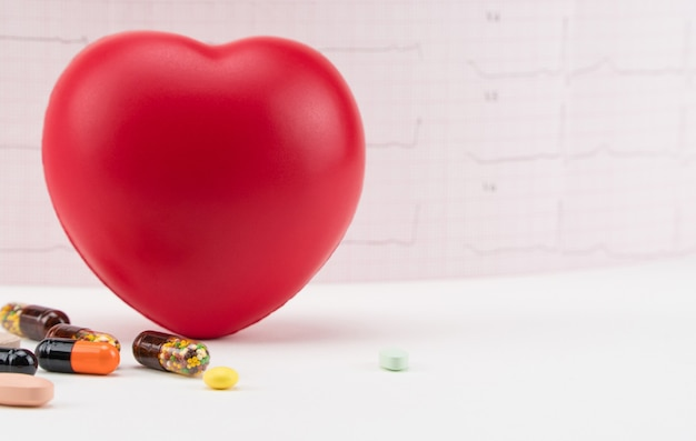 Toy heart with pills on electrocardiogram background cardiology  care of the heart