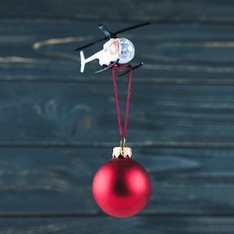 Toy helicopter carrying christmas ornament