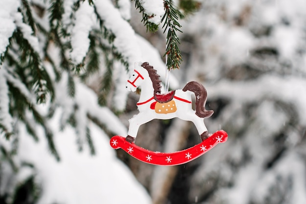 Toy horse on a snow-covered fir branch.