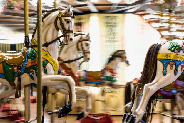 Toy horses on a traditional fairground vintage carousel