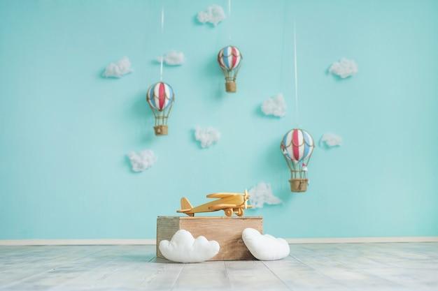 Игрушечные воздушные шары, самолет и облака на синей стене