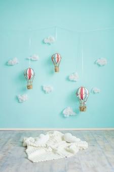 Игрушечные воздушные шары и облака на синей стене