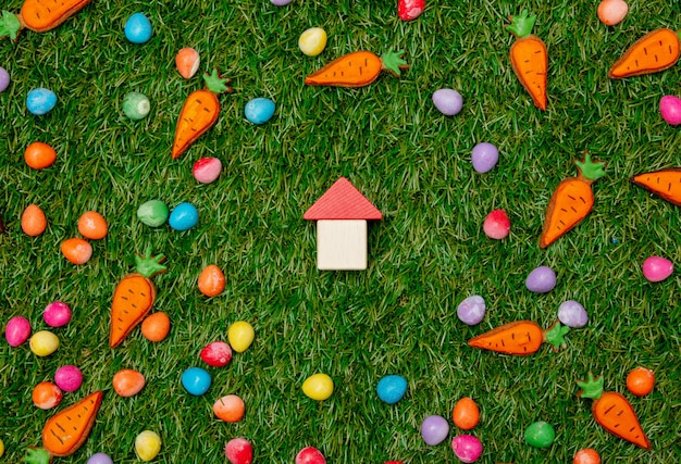 Toy house and cookies with easter eggs on green grass