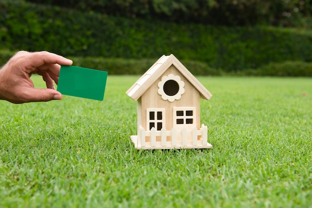 Toy house and credit card in hands invest in real estate concept