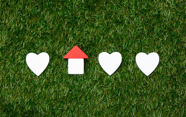 Toy house and heart shapes on green grass.