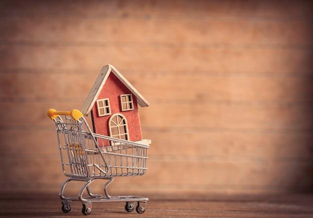 木製のテーブルの上の小さなショッピングカートのおもちゃの家