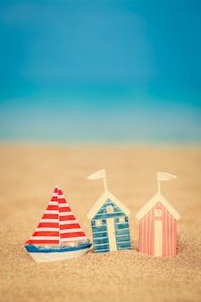 青い海と空を背景に砂浜のおもちゃの家
