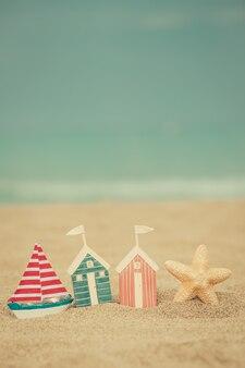 青い海を背景にした砂浜のおもちゃの家