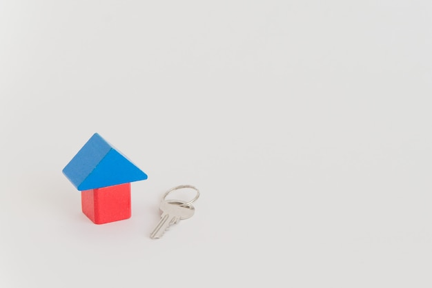 Toy house and real metal key on the white space