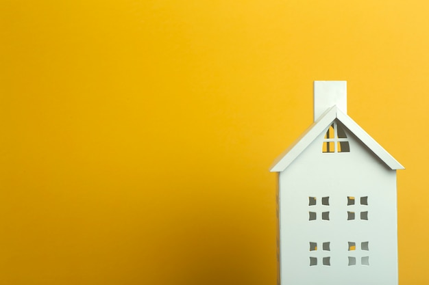 Toy house on yellow background. real estate, rental housing and house concept.