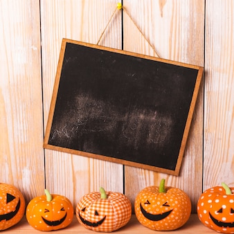 Toy jack-o-lanterns near chalkboard