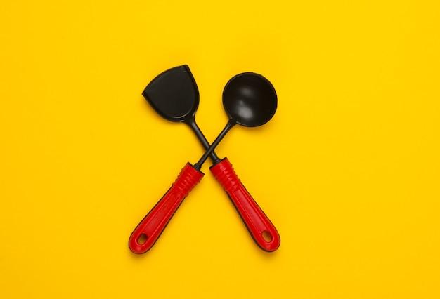 黄色のおもちゃのキッチンツール。キッチンヘラ、おたま。